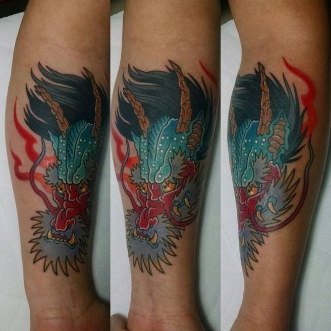 Simple multicolored forearm tattoo of Asian dragon head