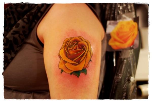 Simple painted big orange rose tattoo on shoulder