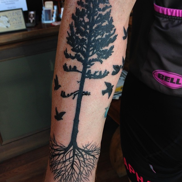 Simple painted black ink tree with roots tattoo on forearm combined with flying birds