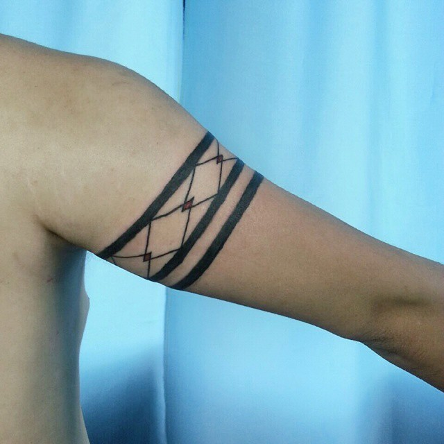 Simple painted colored upper arm tattoo of geometrical ornaments