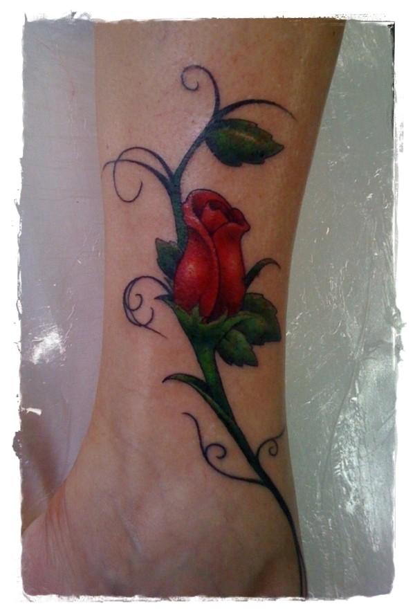 semplice dipinto piccola rosa rossa con foglie tatuaggio su caviglia