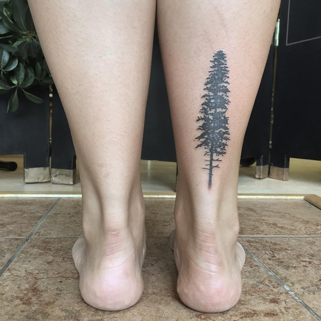 Simple painted tiny black ink ankle tattoo of lonely tree