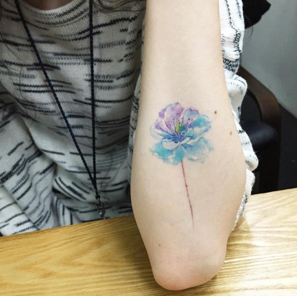 Simple tiny watercolor like colored flower tattoo on forearm
