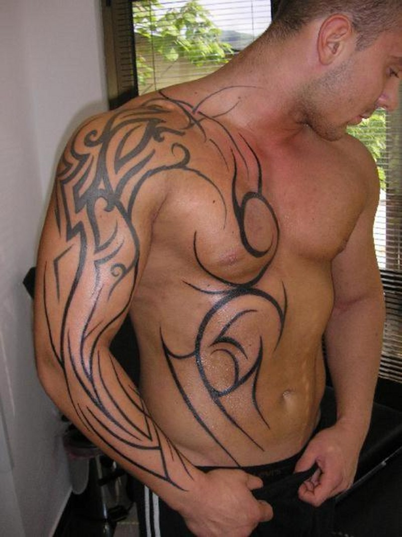 Simple unfinished black ink sleeve and chest tattoo of various tribal ornaments