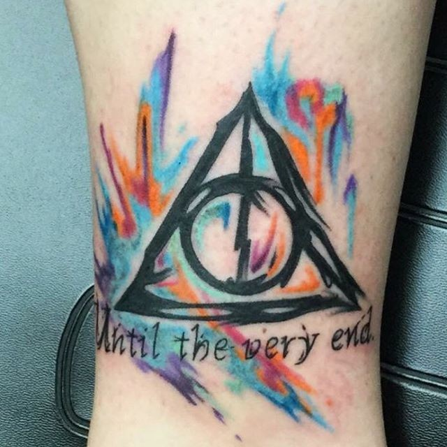 Simple watercolor like colorful triangle tattoo on ankle stylized with lettering