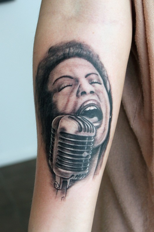 Singing lady and old microphone black and white portrait tattoo on forearm in realism style