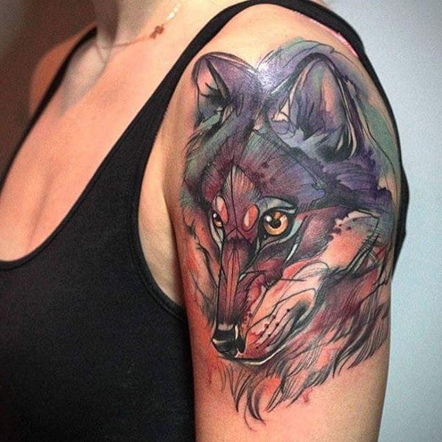 Sketch art style colored upper arm tattoo of original looking wolf