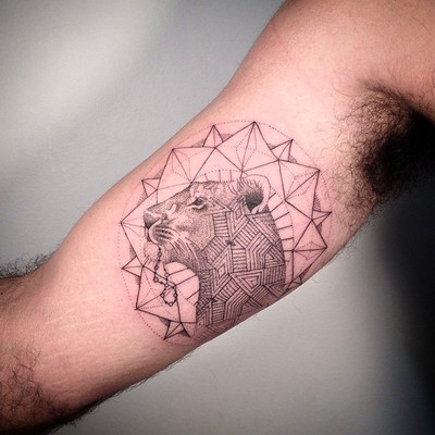 Sketch style black ink biceps tattoo of lion head with ornaments