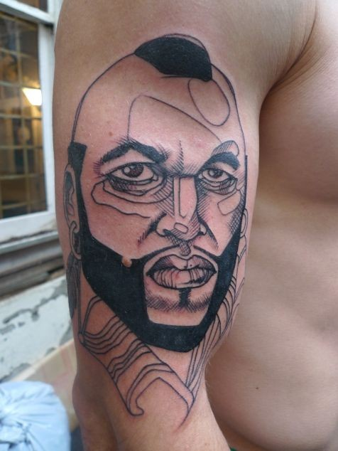 Sketch style black ink shoulder tattoo of famous actor face