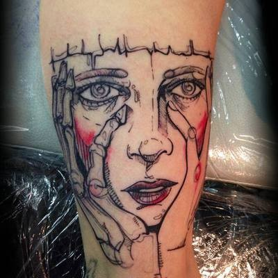 Sketch style colored arm tattoo of creepy woman face