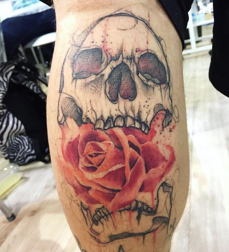Sketch style colored leg tattoo of human skull with red rose