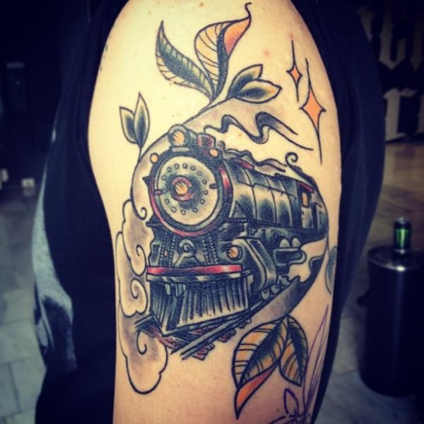 Sketch style colored upper arm tattoo of large train stylized with stars and leafs