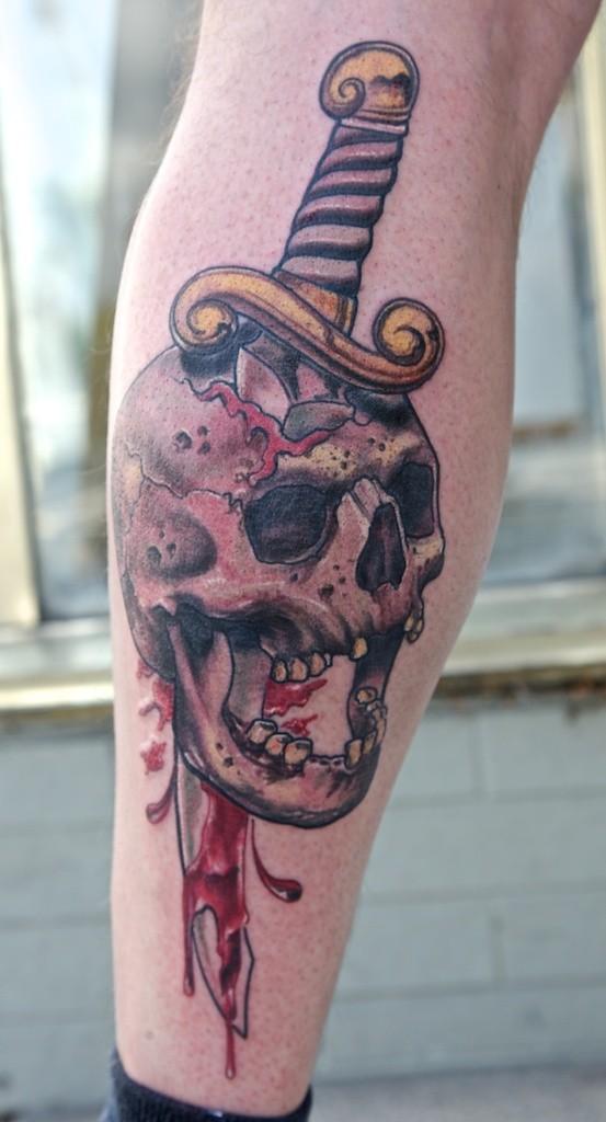 Tatuaggio mostruoso sul braccio il coltello nel teschio