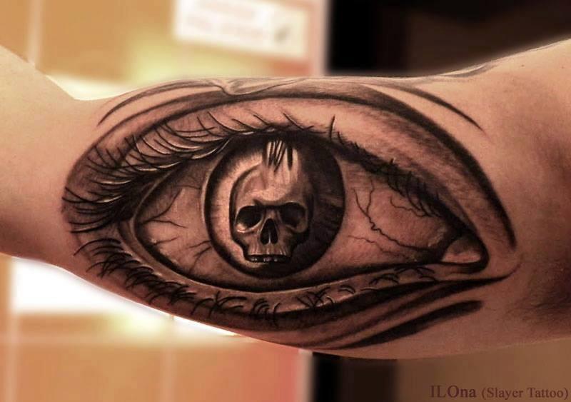 Skull in eye pupil tattoo on arm