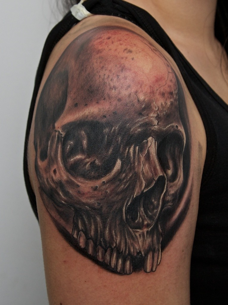Tatuaggio terribile sul deltoide il teschio nero