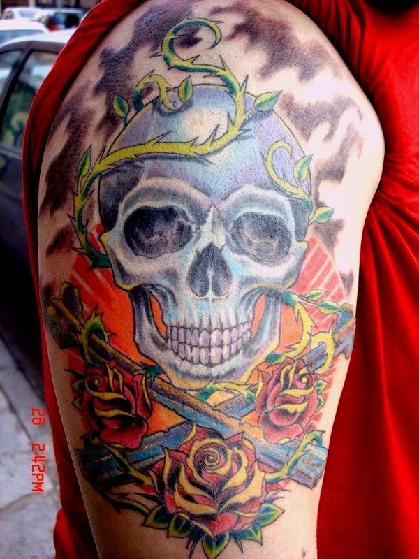 Tatuaggio colorato sul deltoide il teschio & le rose & le spade