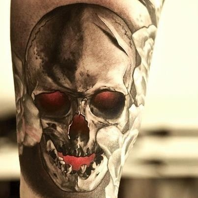 Black evil skull tattoo with red eyes