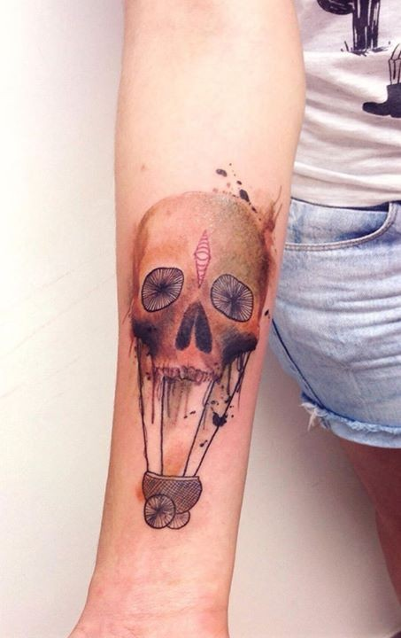 Skull transform in carriage forearm tattoo by Cassio Magne