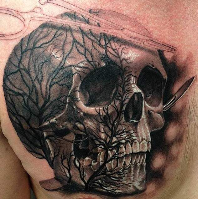 Skull with a tree and medical instruments tattoo on chest