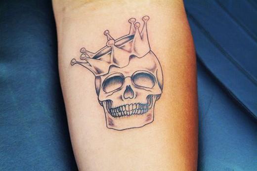 Tatuaggio piccolo bianco nero il teschio con la corona