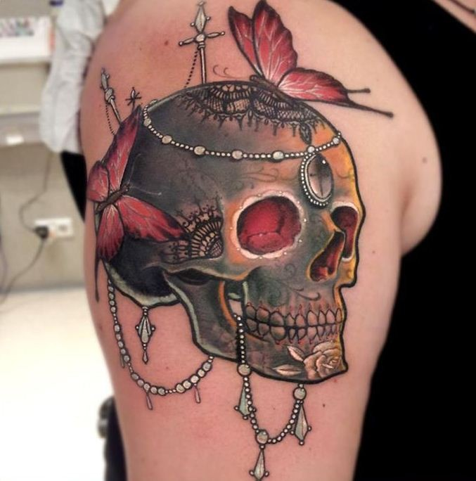 Skull with jewelery and red butterflies tattoo on shoulder