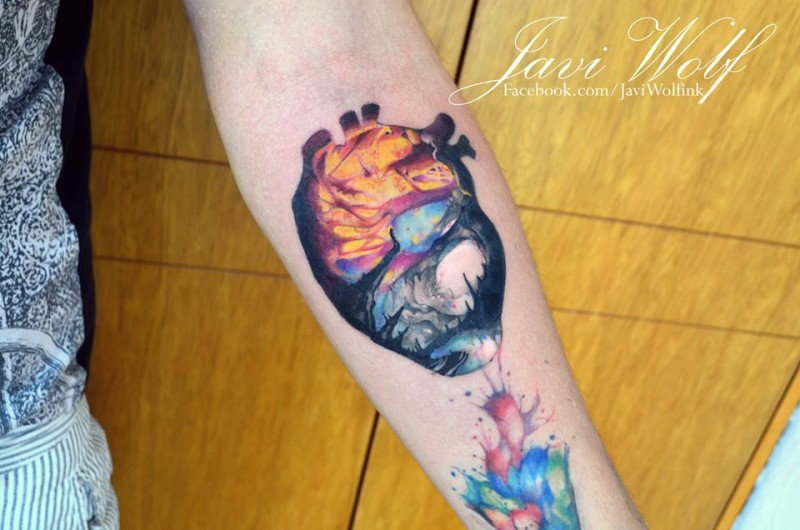 Smal new school style colored forearm tattoo of human heart stylized with mystical forest