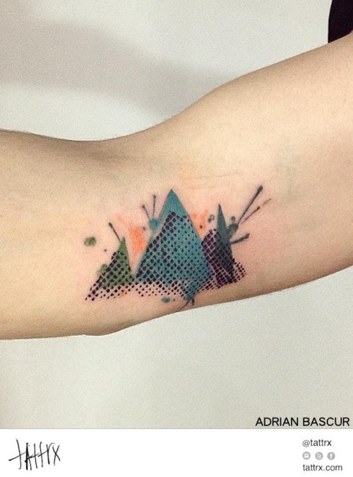 Small abstract style colored mountains tattoo on elbow