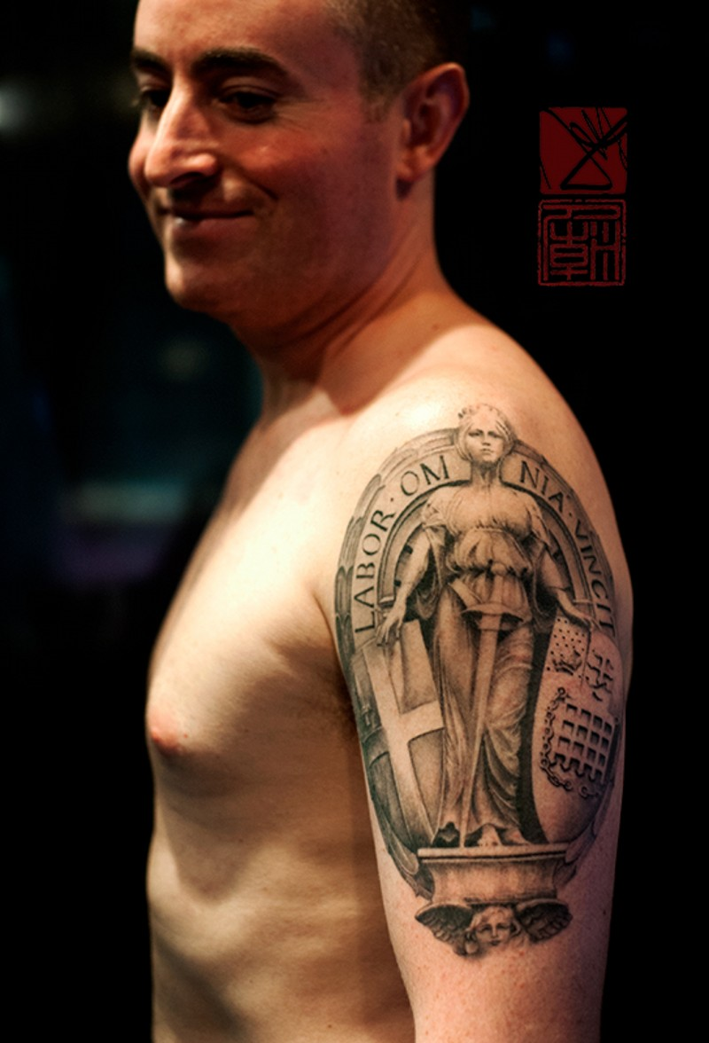 Small black and white antic statue tattoo on shoulder with lettering