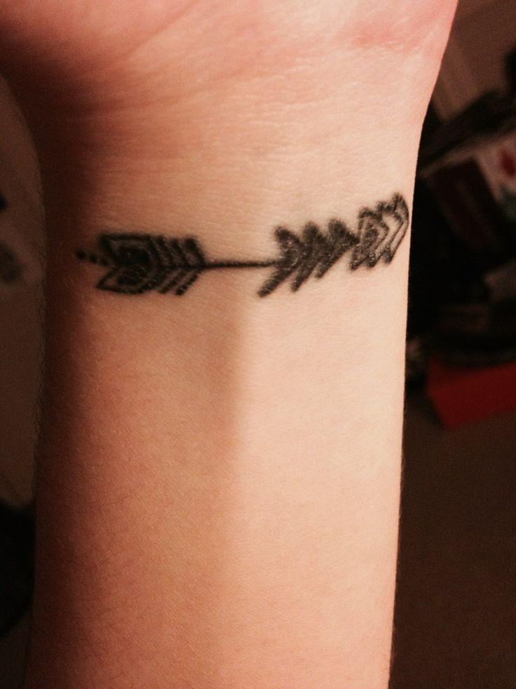 Small black arrow tattoo on girls wrist