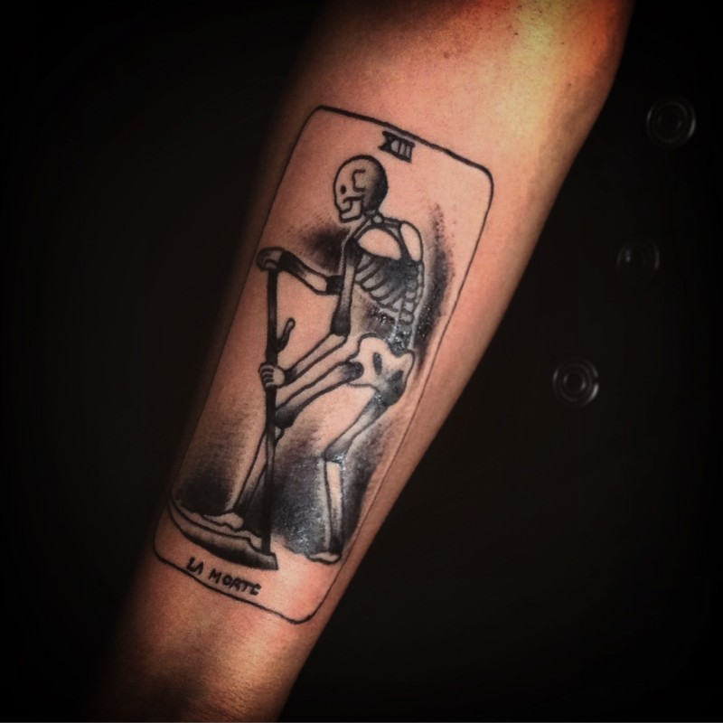 Small black ink arm tattoo of card stylized with skeleton and lettering