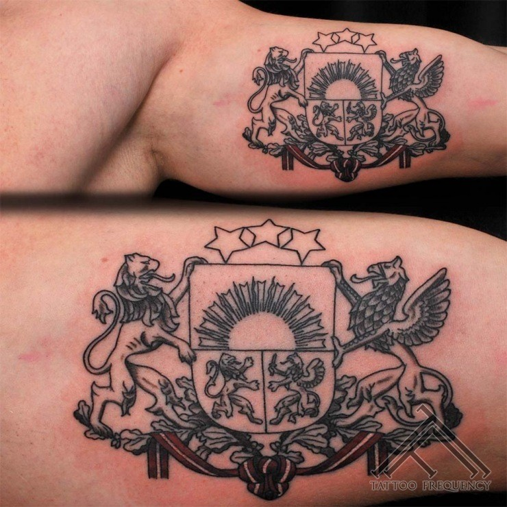 Small black ink biceps tattoo of ancient emblem
