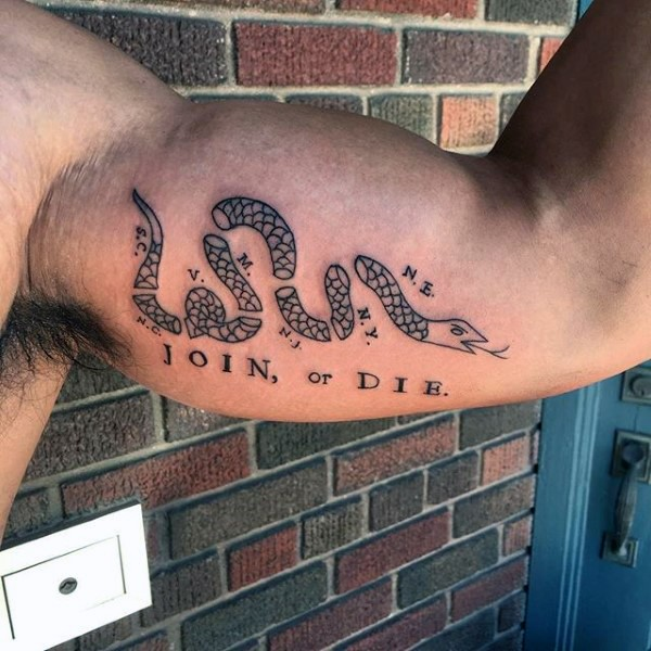 Small black ink biceps tattoo of typical join or die snake symbol with lettering