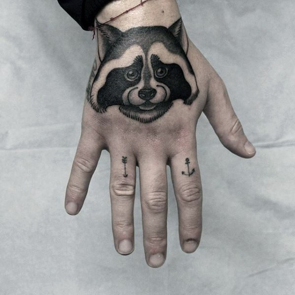 Small black ink cute looking hand tattoo of raccoon with symbols