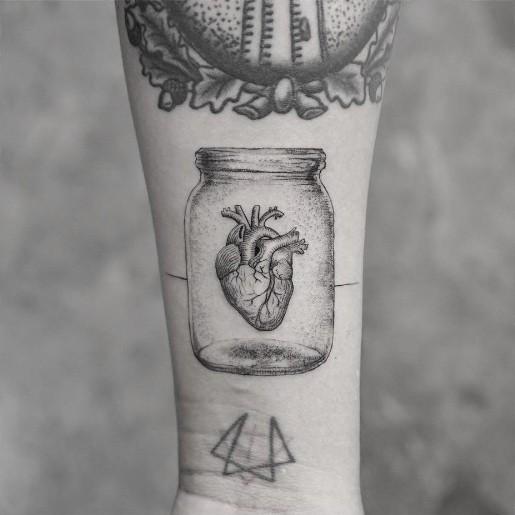 Tatuaggio di vetro con avambraccio di inchiostro nero a pois con cuore umano