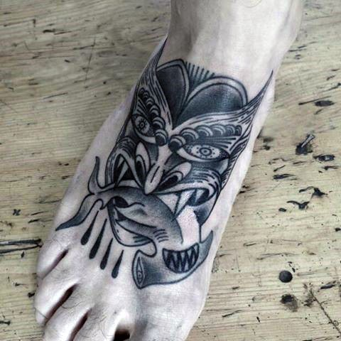 Small black ink engraving style demon with hammerhead shark tattoo on foot