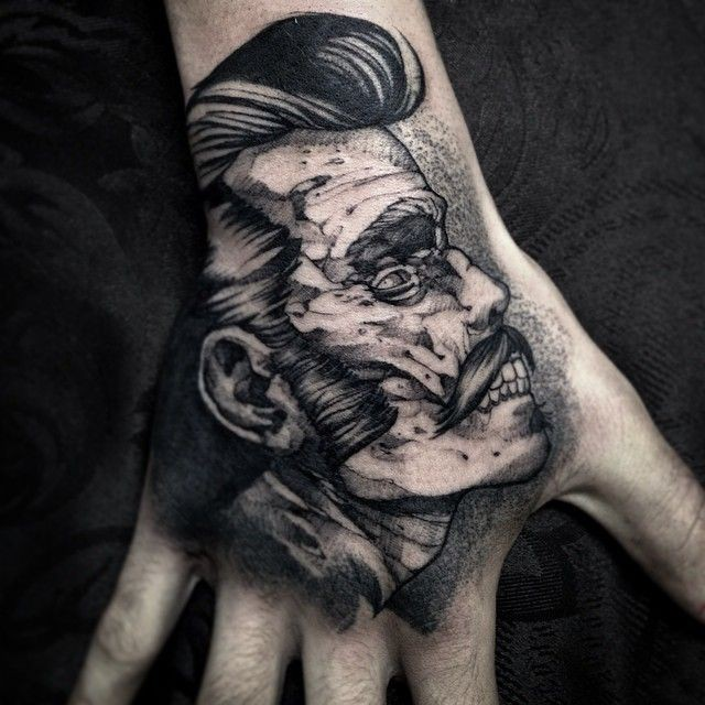 Small black ink engraving style monster zombie face tattoo on hand