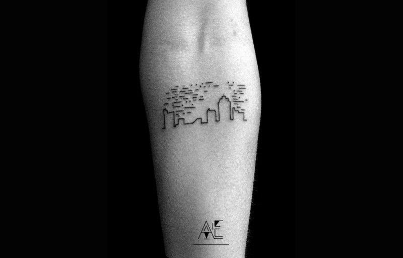 Small black ink forearm tattoo of city sights