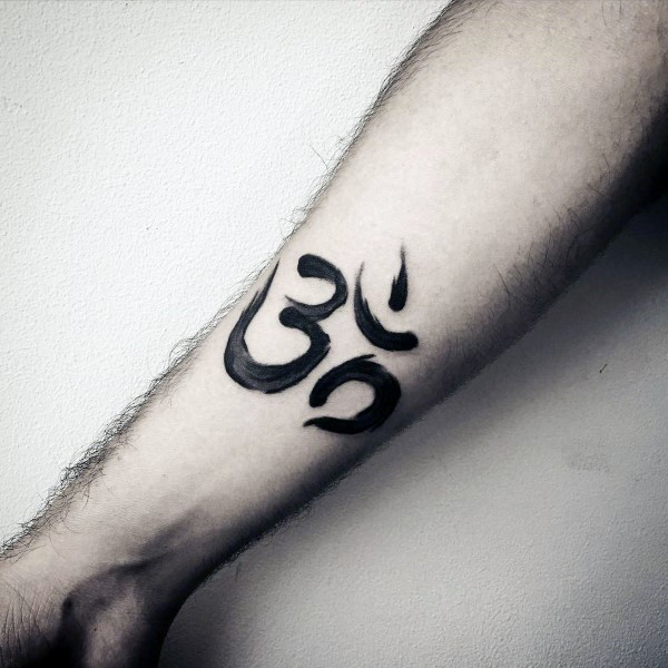Small black ink forearm tattoo of Hinduism symbol