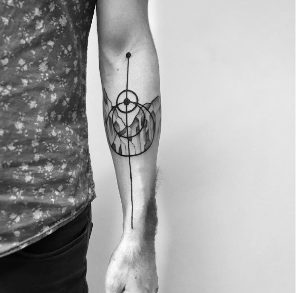 Small black ink forearm tattoo or circles with mountains