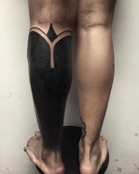Small black ink leg tattoo of various ornaments
