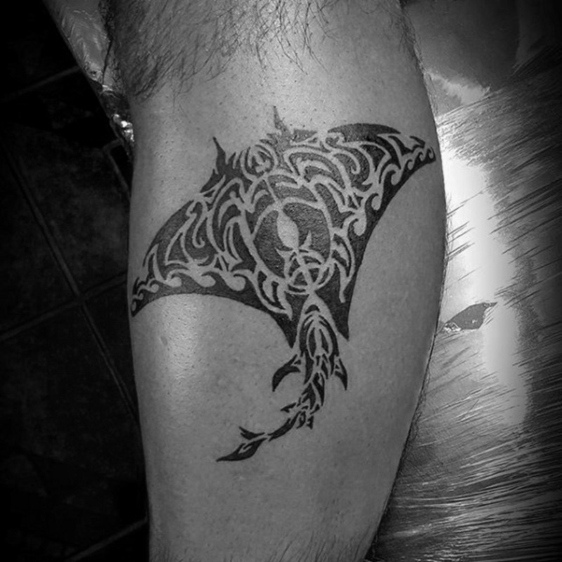 Small black ink ray tattoo on leg stylized with tribal ornaments