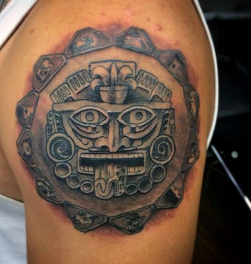 Small black ink shoulder tattoo of Mayan tablet