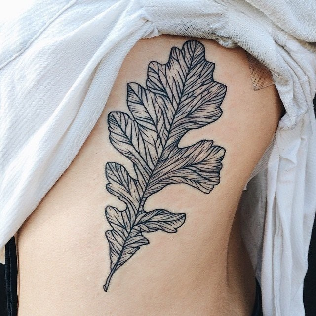 Small black ink side tattoo of typical leaf