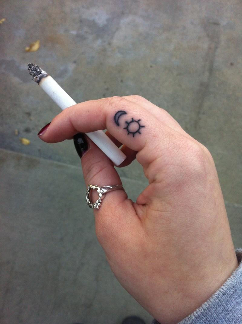 Tatuaje en el dedo, signos de sol y luna