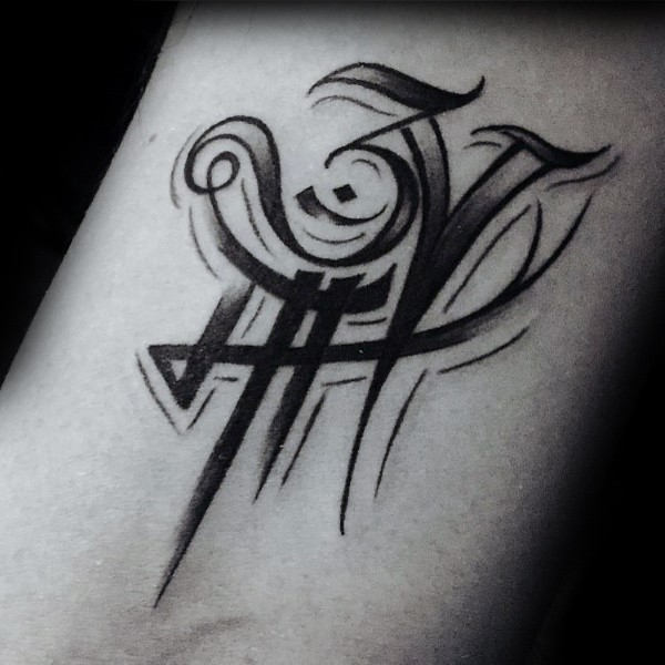Small black ink symbol tattoo on arm