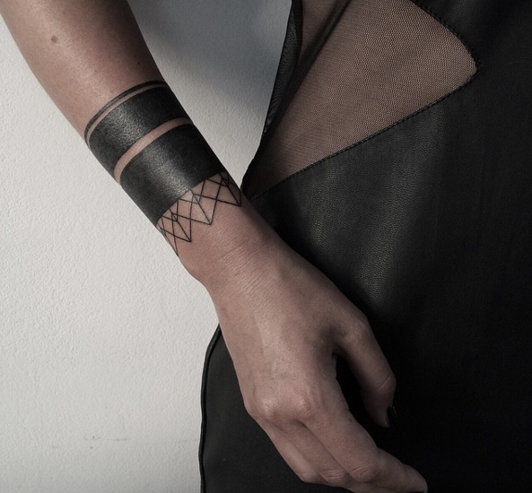 Small black ink wrist tattoo of simple ornament