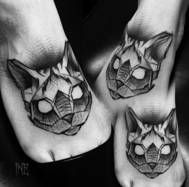 Small blackwork style foot tattoo of cat head by Inez Janiak