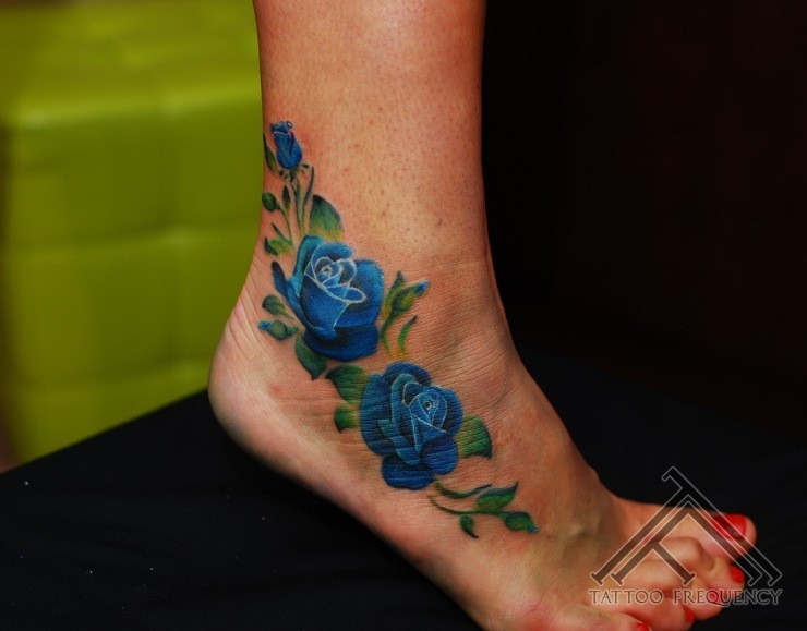 Small blue colored ankle tattoo of large roses