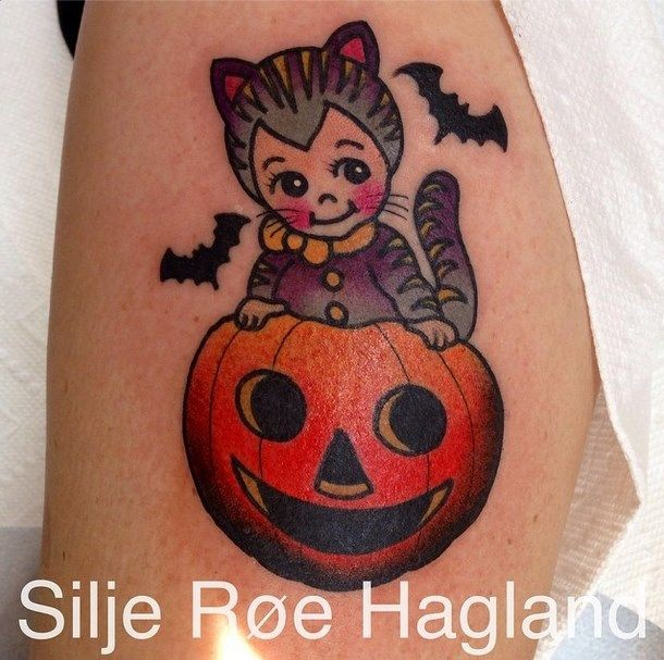 Small cartoon style arm tattoo of little kitten with pumpkin
