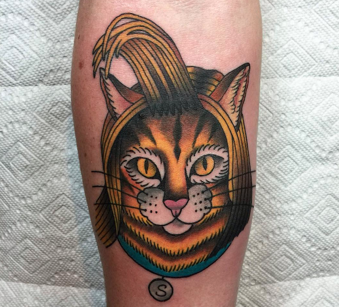 Small cartoon style colored cat face tattoo on forearm